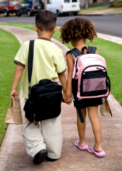 Siblings-with-backpacks-on-way-to-school
